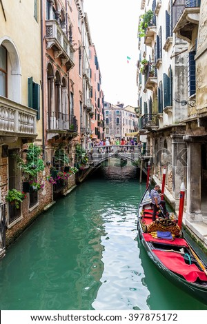 VENICE, ITALY - June 26, 2014: Tourists travel on gondolas in Venice, Italy. Gondola ride is the most popular tourist activities in Venice. #397875172