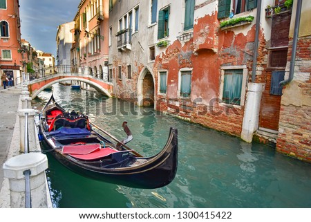 Venice / Italy - November 26 2018: Gondola, the traditional Venetian boat, on canal with tourists, Venice, Italy #1300415422
