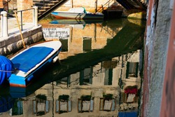 Venice, Italy. Reflections of buildings in the water in one of the Venetian canals, next to a moored boat and a fragment of the bridge.