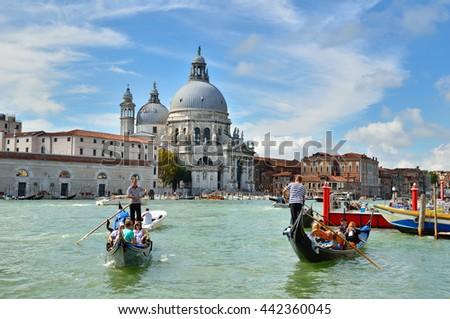 Venice, Italy - September 10, 2014: Grand Canal with Basilica di Santa Maria della Salute in the background. Tourists ride on a gondola. #442360045