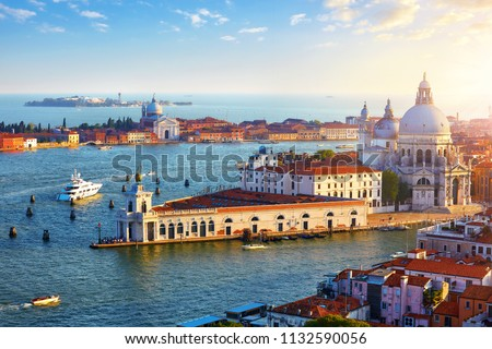 Venice Italy. Top view at Cathedral of Santa Maria della Salute in district Dorsoduro and island Giudecca. Evening sunset yachts on sea water.