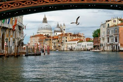 Venice, Italy. View from vaporetto on the Grand Canal just in front of the Accademia Bridge. Behind the bridge, a panorama of the city with architectural pearls and the calm waters of the canal.
