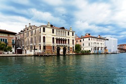 Venice, Italy. View of the Grand Canal and the surrounding buildings. Calm water of the canal and beautiful blue sky with white clouds. Tourists' breathtaking architecture of the decadent town.