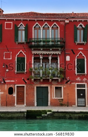 Venice: lovely 15th Century red palace, with gothic windows and balconies with flowers. Venezia, Italy.