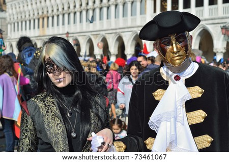 VENICE - MARCH 7: Two unidentified masked persons in costume in St. Mark's Square during the Carnival of Venice on March 7, 2011. The 2011 carnival was held from February 26th to March 8th.