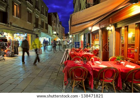 VENICE - NOV 13: Outdoor restaurant with red tables and chairs - one of the many bars and restaurants popular with tourists in the evening hours on streets of Venice, Italy on November 13, 2012.