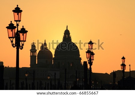 Venice: silhouette  of Cathedral Santa Maria della Salute and street lamps at sunset