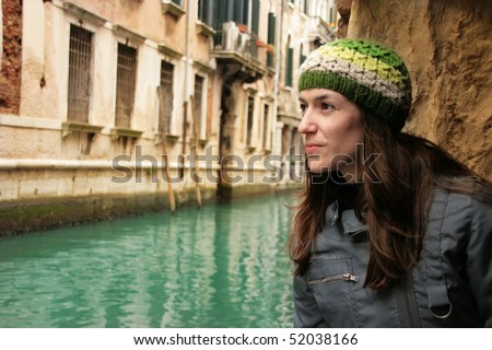 Venice: Young attractive woman as a tourist looking at the romantic canals of Venezia.
