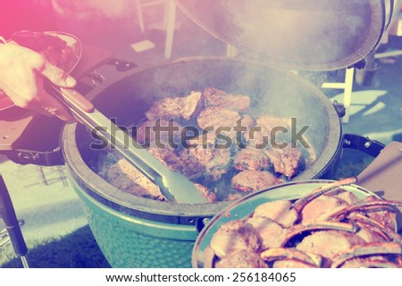Venison being fried on grill at outdoor kitchen