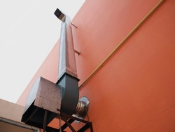 Ventilation chimney on the wall. Made of zinc for air intake in restaurant kitchens. On the background, orange wall and white sky with copy space. Focus close and choose the subject.