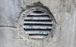ventilation hole in concrete. Metal industrial round ventilation cover. Rusty and dirty old round ventilation frame with horizontal metal stripes.