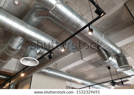 Ventilation pipes in silver insulation material hanging from the ceiling inside new building. Stockfoto ©