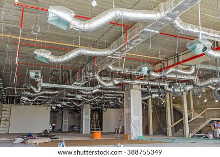 Ventilation pipes in silver insulation material hanging from the ceiling inside new building. stock photo