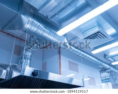 Ventilation system on ceiling of industrial room. Air purification system in restaurant. Pipes from the hood on ceiling, bottom view. Air purification system in an industrial kitchen.