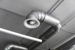 Ventilation system on the ceiling of large buildings. Ventilation pipes in silver insulation material hanging from the ceiling inside new building.