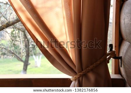 Veranda with beige curtains and rope hooks. Rope hooks on metal hooks