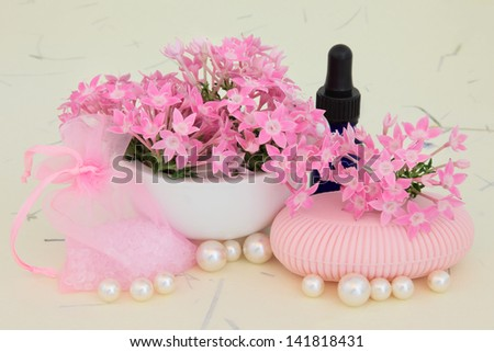 Verbena flowers with aromatherapy essential oil bottle, pink soap, bath crystals and pearls over mottled cream background.
