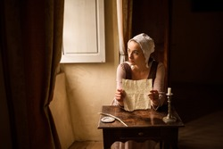 Vermeer style portrait of a young maid in renaissance costume reading a letter at her window