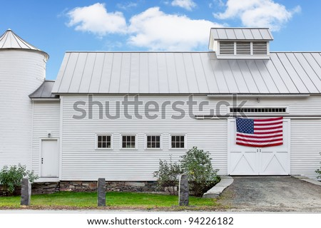 Vermont white dairy barn. Vintage 19th century barn with American flag hanging across the doors