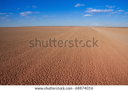 Verneukpan, South Africa, large flat desert pan where land speed records are attempted with car disappearing in the distance - stock photo