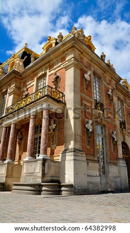 Versailles Palace facade and golden fence over blue sky. France