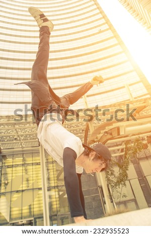 vertical action move in business center. young boy performing parkour moves.