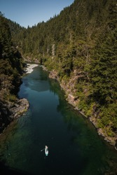 Vertical aerial picture paddle boarder on standup paddle board paddling up river in summer exploring wild nature on remote river. Leisure sport recreation in idyllic Smith River northern California
