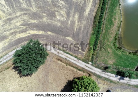 Vertical aerial view over a path next to a harvested field and a meadow with a small stable near a narrow moat.. Stock fotó ©
