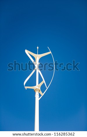 Vertical axis wind turbine against a clear deep blue sky