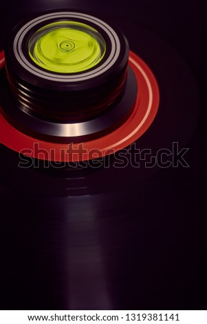 Vertical background of a rotating record and weight with a diagonal flare to the lower right. #1319381141