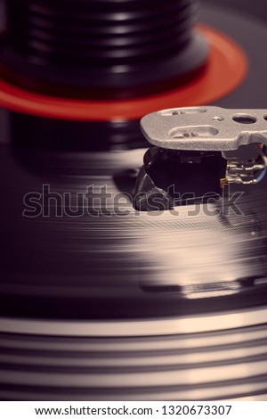 Vertical background of a rotating record and weight with the stylus lowered and a flare highlighting the stylus at the mid right. #1320673307