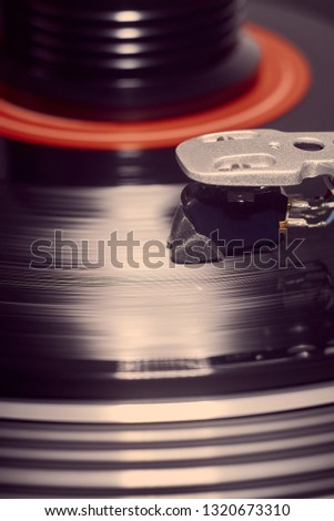 Vertical background of a rotating record and weight with the stylus lowered and a flare highlighting the stylus. #1320673310