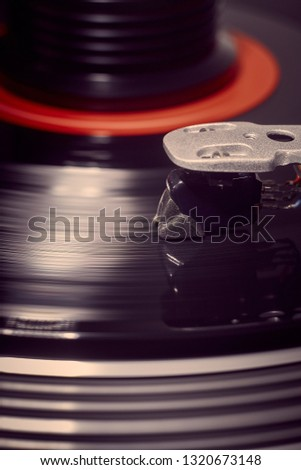 Vertical background of a rotating record and weight with the stylus lowered and a strong flare to the left. #1320673148