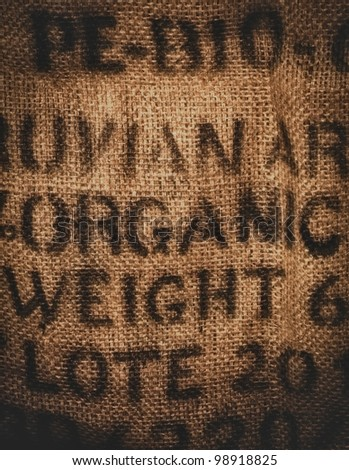 Vertical background of a twenty kilogram hessian coffee bag stamped and certified one hundred percent organic - stock photo