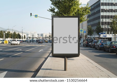Vertical billboard for commercial advertisements standing by busy highway in city center. Digital solutions for promotional campaigns, great way to draw attention to product and service ads outdoors.