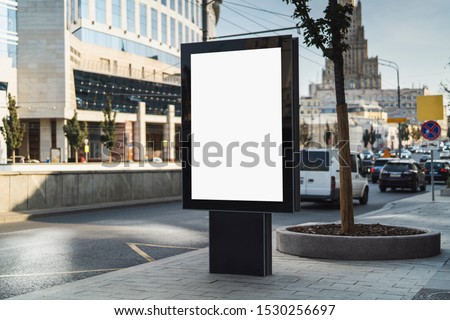 Vertical billboard for dispaying commercials in street. Cars and public transport passing by. Urban architecture of big city in background. Sidewalk for pedestrians, great place for promotional ads.