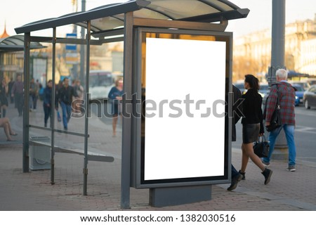 Vertical billboard in the city advertising in the bus shelter. for placing the MOCKUP advertisement with people in the background Outdoor Advertising