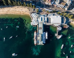Vertical bird's eye aerial evening drone view of Manly wharf, part of the oceanside suburb of Manly, Sydney, New South Wales, Australia. Three ferries docked at the wharf. Manly Cove beach to the left