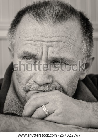 vertical black and white head shot image  of a middle aged man with facial hair and must ache and sober expression with chin resting on his hand.