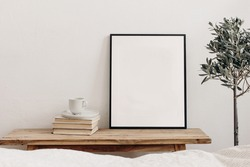 Vertical black picture frame mockup on vintage bench, table. Cup of coffee on pile of books. Potted olive tree. White wall background. Scandinavian interior, neutral color palette. Selective focus.
