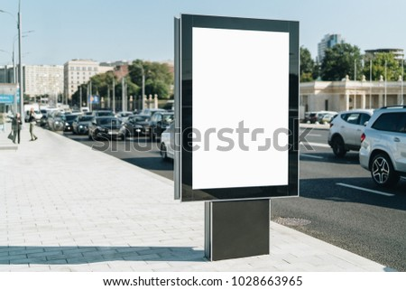 Vertical blank glowing billboard on the city street. In the background buildings and road with cars. Mock up. The poster on the street next to the roadway.