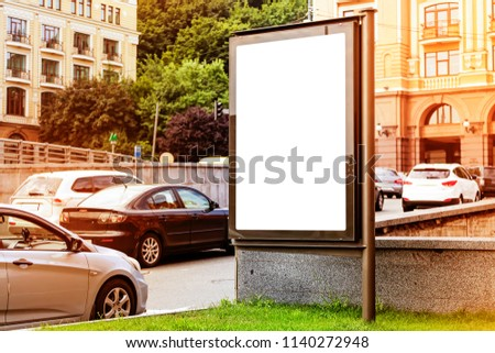 Vertical blank white billboard on a city street. In the background of the building and the road. A billboard in the street next to the roadway. Layout. Sunny summer day.