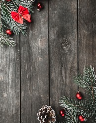 Vertical Christmas theme with fir branches, red bows and globes, cones, on rustic dark wooden background viewed from above, top, greeting card with space for text