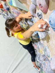 VERTICAL, CLOSE UP, DOF: Athletic female with taped fingers climbs up a colorful bouldering wall. Fit young woman reaches up to grip a yellow jug hold while exercising at an indoor climbing gym.