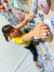 VERTICAL, CLOSE UP, DOF: Fit young woman reaches up to grip a yellow jug hold while exercising at an indoor bouldering gym. Athletic female with taped fingers climbs up a colorful climbing wall.