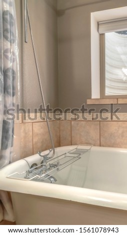 Vertical Close up of a bathtub in side a bathroom with shower curtains and window #1561078943