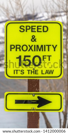 Vertical Close up of a bright yellow Speed and Proximity road sign with arrow #1412000006
