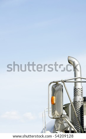 Vertical close-up of a truck's mirrors and exhaust pipe against the sky giving copy space, contrast of bright blue sky and pollution source - environmental concept.