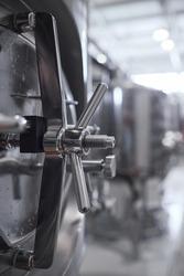 Vertical close up of secured hatch on steel barrel at industrial workshop, copy space
