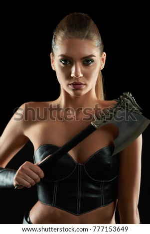 Vertical close up portrait of a gorgeous female viking posing aggressively with an axe on black background beauty brutality savage warrior Amazon culture fighter battledress weapon.